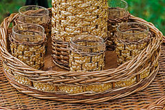 Glasses and bottle wrapped in wicker Royalty Free Stock Photos