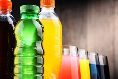 Glasses and bottles of assorted carbonated soft drinks. In variety of colors Stock Photos