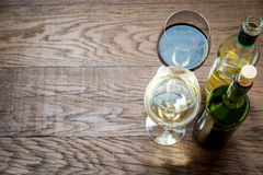 Glasses and bottles with red and white wine. On the wooden table royalty free stock photo