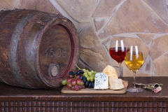 Glasses and bottles of wine, cheese on old  barrel Royalty Free Stock Images