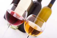 Glasses and bottles of wine unusually on white Royalty Free Stock Photos