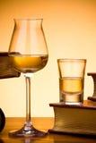 Glasses of brandy near books Stock Images