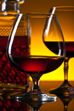 Glasses of brandy on the reflective background Royalty Free Stock Image