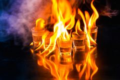 Glasses with burning alcohol on black background Stock Image