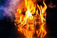 Glasses with burning alcohol on black background Stock Image