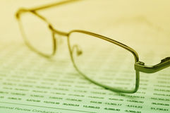 Glasses on business graph, financial concept stock images