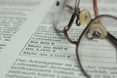 Glasses on business report. Glasses lying on business report with German text and euro symbol Royalty Free Stock Photo