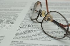 Glasses on business report. Glasses lying on business report with German text and euro symbol stock images