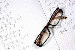Glasses and calculations. Glasses on Binci sheet with calculations stock photos