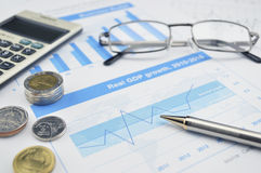 Glasses, calculator and coin on financial chart and graph, accou Stock Photography