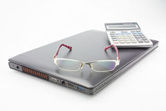 Glasses and calculator on modern laptop. Isolated over white Royalty Free Stock Photos