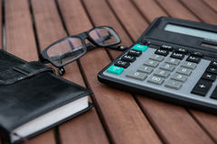 Glasses, calculator, notepad on wooden table Royalty Free Stock Image