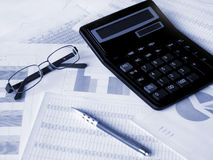 Glasses, calculator and pen on financial documents. Toned blue. Shallow DOF Royalty Free Stock Photo