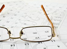 Glasses on the calendar pages. Stock Photography