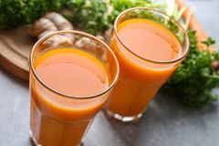 Glasses of carrot juice. On light table royalty free stock photos