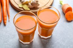 Glasses of carrot juice. On light table stock image