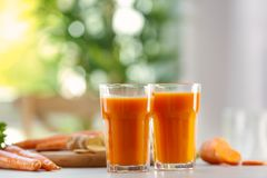 Glasses of carrot juice. On light table stock photo