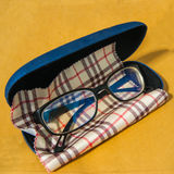 Glasses with case and cleaning cloth. On brown background Royalty Free Stock Image