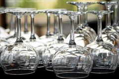Glasses for Catering. Many wine and water glasses under lights on a table for a catered event/reception/party (shallow focus on the foreground glasses stock images