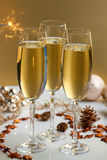 Glasses of champagne. Three glasses of champagne, christmas balls and ornaments in front of golden background Royalty Free Stock Photo