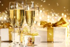 Glasses of champagne. With gold ribboned gifts Royalty Free Stock Photo