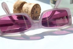 Glasses and champagne. Violet sunglasses and a cork Stock Photo
