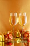 Glasses with champagne. Two glasses with champagne and gifts on gold background royalty free stock images