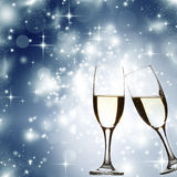 Glasses with champagne against blue holiday lights Royalty Free Stock Image