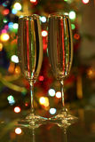 Glasses with champagne against festive lights Stock Photos