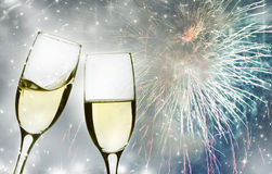 Glasses with champagne against fireworks and clock Stock Photos
