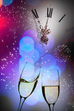 Glasses with champagne against fireworks and clock Royalty Free Stock Images