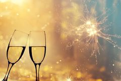 Champagne glasses on sparkling background. Glasses with champagne against fireworks and holiday lights - Celebrating the New Year Royalty Free Stock Photos