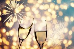 Champagne glasses on sparkling background. Glasses with champagne against fireworks and holiday lights - Celebrating the New Year Royalty Free Stock Image