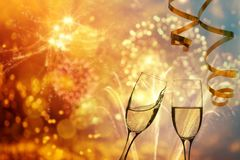 Champagne glasses on sparkling background. Glasses with champagne against fireworks and holiday lights - Celebrating the New Year Stock Photography