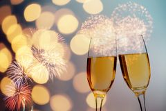 Champagne glasses on sparkling background. Glasses with champagne against fireworks and holiday lights - Celebrating the New Year Stock Image