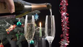 Glasses with champagne against holiday candle stock video footage