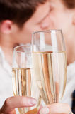 Glasses of champagne against lovers Stock Photography