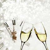 Glasses with champagne andclock against holiday lights Royalty Free Stock Photos