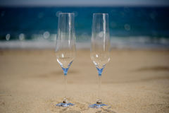 Glasses of champagne on the beach, background. Glasses of champagne on the sandy beach, sea background Stock Image