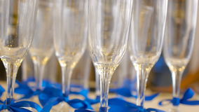 Glasses of champagne with blue ribbons, set. Glasses of champagne with blue ribbons on table, set stock footage
