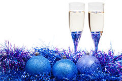 Glasses of champagne and blue and violet baubles Royalty Free Stock Photography
