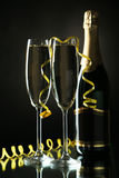 Glasses of champagne with bottle on a black Royalty Free Stock Photo