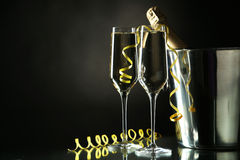 Glasses of champagne with bottle in a bucket on black Royalty Free Stock Image