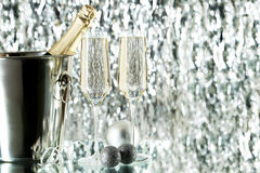 Glasses of champagne with bottle in a bucket on lights Stock Images
