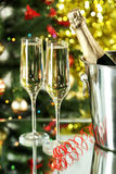Glasses of champagne with bottle in a bucket on lights Royalty Free Stock Photography