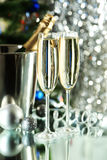 Glasses of champagne with bottle in a bucket on lights background, close up Royalty Free Stock Photos