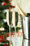 Glasses of champagne with bottle in a bucket on lights background, close up Royalty Free Stock Images