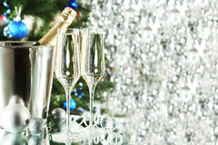 Glasses of champagne with bottle in a bucket on lights background, close up Royalty Free Stock Photo