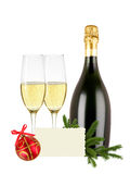 Glasses of champagne, bottle, greeting card and red christmas ba. Ll and tree branch isolated on white background Stock Photos