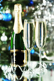 Glasses of champagne with bottle on a lights background Royalty Free Stock Photography